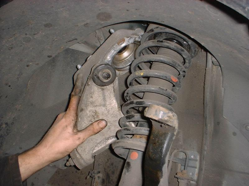<p>8. Ease the wishbone and mounting bracket out from above the shock absorber (it will come out honest).